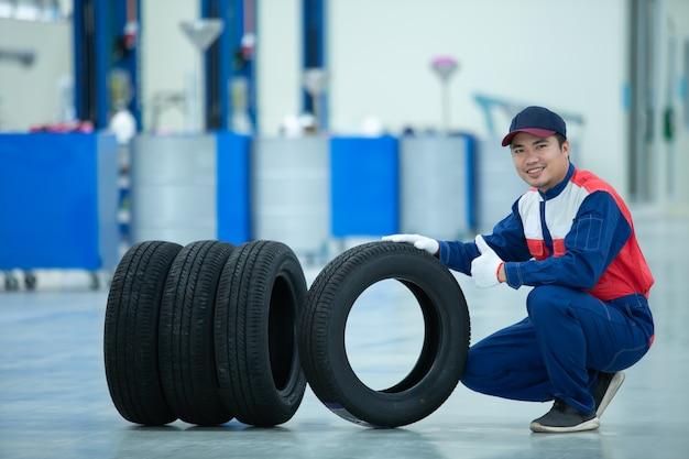 Der gutaussehende asiatische mechaniker in uniform sitzt und hält das autoreifenrad mit dem daumen nach oben im autoreparaturzentrum