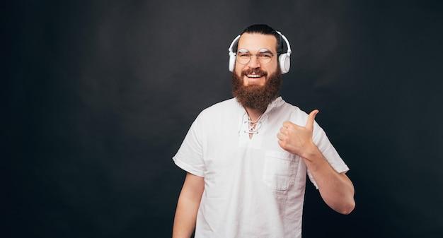 Der gutaussehende bärtige mann hält einen daumen hoch und trägt ein headset, das einen podcast oder musik hört.