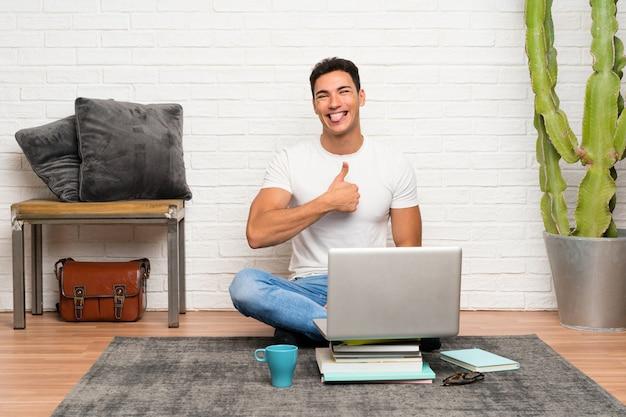 Der gutaussehende mann, der auf dem boden mit seinem laptop gibt daumen sitzt, up geste