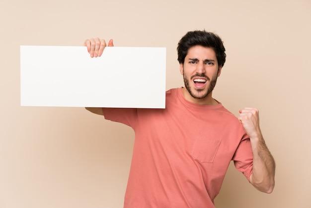 Der gutaussehende mann, der ein leeres weißes plakat für hält, fügen ein konzept ein