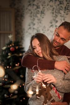 Der gutaussehende mann, der nette frau in den strickjacken umarmt, nähern sich weihnachtsbaum
