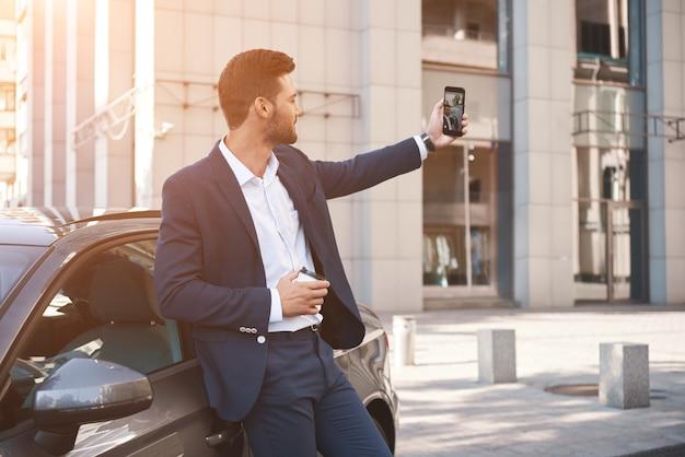 Der gutaussehende mann im autohaus macht ein selfie mit seinem neuen auto, das daumen zeigt und