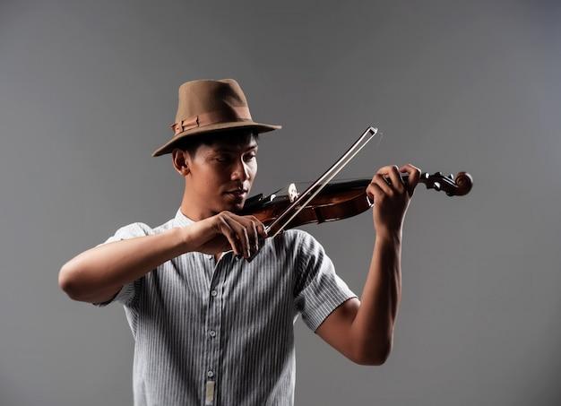 Der gutaussehende mann legte bogenberührung auf schnur, zeigt, wie man violine spielt