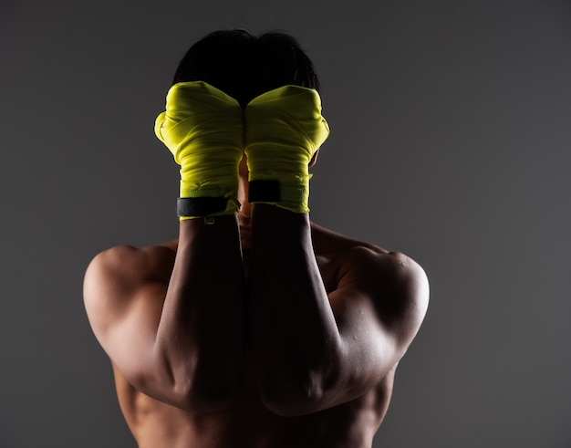 Der gutaussehende mann mit dem gelben fausthandschuh streckte die hände aus, um sein gesicht zu schließen, zeigte die faust und bereitete sich auf das schlagen vor