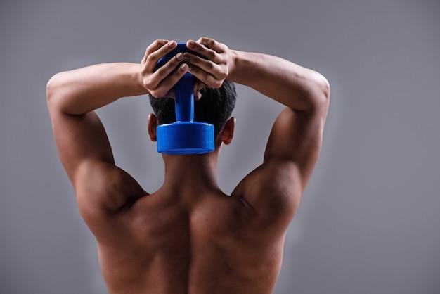 Der gutaussehende mann zeigt sich fit und von der hinteren körperseite, hebt die blaue hantel an, für gebauten arm, muskel- und kunstton