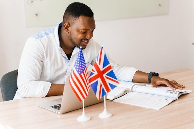 Der gutaussehende schwarze übersetzer nutzt seinen laptop für die online-arbeit entsprechend der sozialen distanzierung