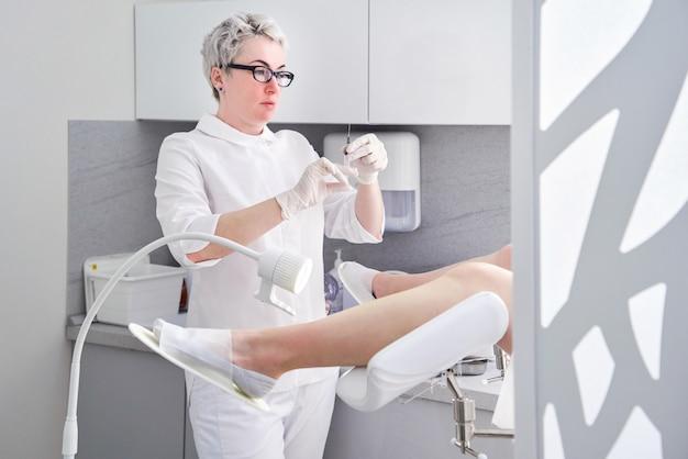 Der gynäkologe mit spritze injiziert dem patienten im gynäkologiestuhl eine injektion