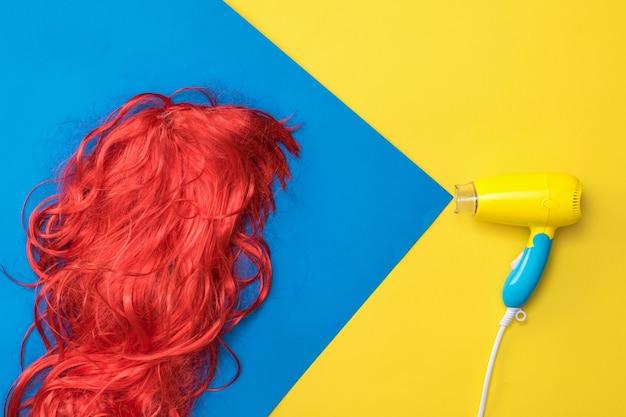 Der haartrockner lenkt einen luftstrahl auf die orangefarbene perücke. haarpflegekonzept. erstellen sie einen neuen stil.