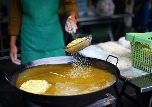 Der händler brät knusprige gelbe nudeln auf dem bratrost in einer großen pfanne mit heißem öl. knusprige eiernudeln für nudeln in dick-chinesisch-thailändischer soße.
