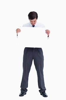 Der händler, der leeres zeichen betrachtet, unterzeichnen herein seine hände