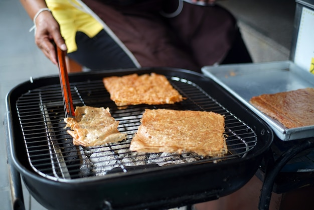 Der händler hat in scheiben geschnittene blätter aus getrocknetem und gewürztem knusprigem schweinefleisch gegrillt, um sie auf dem holzkohleofengrill zu erhitzen.