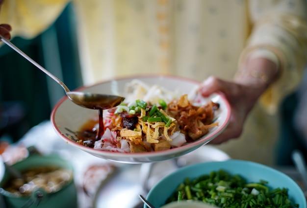 Der händler kocht sojasauce auf köstlichen chinesischen gedämpften reisnudelröllchen, die wunderschön in einem weißen teller angeordnet sind, um den kunden im lokalen restaurant zu bedienen.