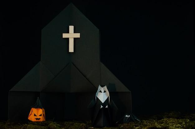 Der halloween-hintergrund des origamis (oder der papierfalte), die die nonne vor schwarzer kirche mit steckfassung-olaterne und spinne mit unordentlichem rasen steht