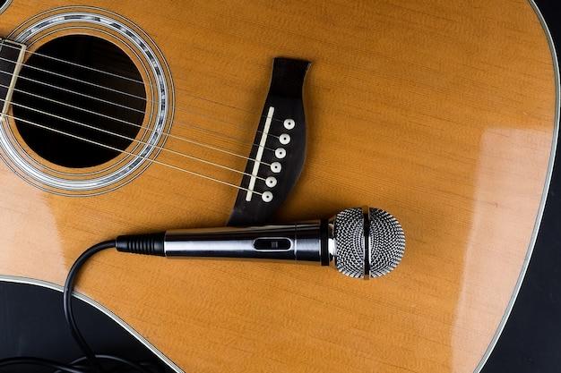 Der hals einer klassischen sechssaitigen gitarre und eines silbernen mikrofons