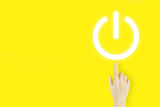 Der handfinger der jungen frau zeigt mit dem hologramm, das die taste auf dem virtuellen bildschirm auf gelbem hintergrund drückt. konzept starten oder herunterfahren konzept zum hochfahren.