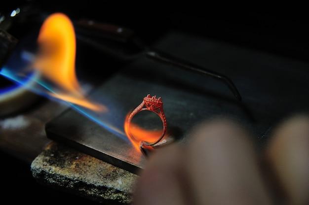 Der handwerker arbeitet mit einem gassprühwerkzeug, um einen ring herzustellen