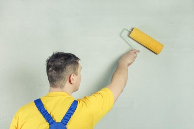 Der handwerker behandelt die wand mit einer grundierung unter verwendung einer walze.