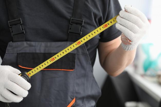 Der handwerker in uniformhandschuhen misst das maßband