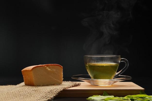 Der heiße grüne tee in der glasschale mit rauch und butterkuchen auf dem holzbrett.