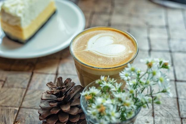 Der heiße latte art coffee mit kuchen