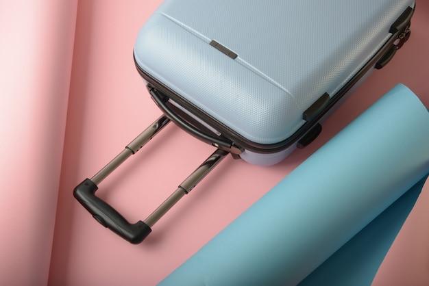 Der hellblaue koffer liegt auf rosa und blauem papier