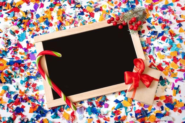 Der helle konfetti-hintergrund mit einkaufstafel und neujahrsdekoration.