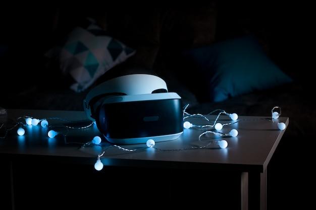 Der helm der virtuellen realität. neue erfahrung im spiel. erstaunliche emotionen, kühle ruhe. virtual-reality-brillen liegen in neonlichtern.