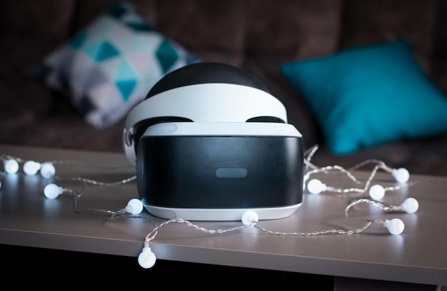Der helm der virtuellen realität. neue erfahrungen im spiel gesammelt. erstaunliche emotionen, kühle ruhe, neustart. virtual-reality-brillen liegen in neonlichtern auf dem tisch