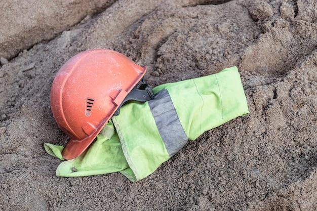 Der helm und die signalweste eines orangefarbenen bauarbeiters ruhen auf einem sandhaufen, um beton vorzubereiten. mittagspause auf einer baustelle.