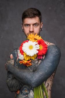 Der hemdlose junge mann mit tätowiert auf seinem körper, der den schönen gerbera hält, blüht in der hand gegen grauen hintergrund