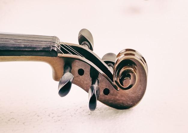 Der hintergrund der abstrakten kunstentwurf der rolle und der pegbox der violine, undeutliches licht herum