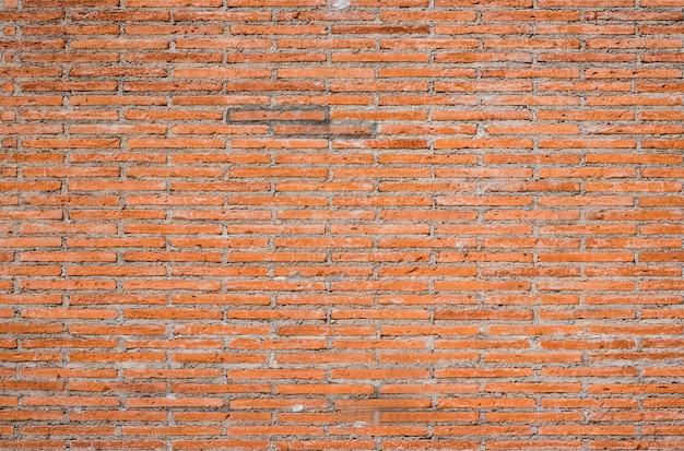 Der hintergrund der backsteinmauer mit dunklem orange wird schön vereinbart. alte mauer grunge hintergrund der hintergrund kann im innenraum verwendet werden.