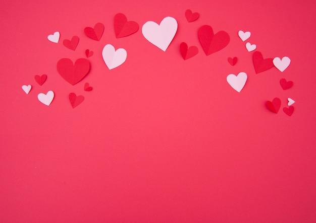 Der hintergrund des st.-valentinsgrußes mit den rosa und roten papierherzen