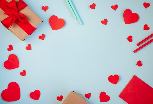 Der hintergrund des valentinstags. geschenke, herzen, cocktailgefäße, band im pastellblau. das konzept des valentinstags. draufsicht, kopie, raum