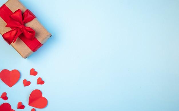 Der hintergrund des valentinstags. geschenke, herzen, rotes band auf blauen pastelltönen. das konzept des valentinstags. draufsicht, kopie, raum