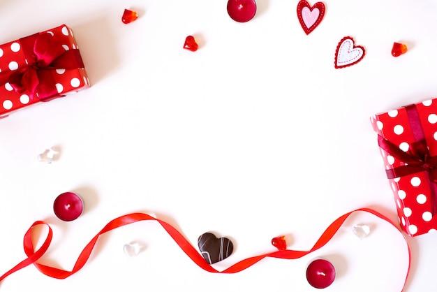 Der hintergrund des valentinstags. geschenke mit bögen, kerzen, konfetti, rotem satinband, herzen auf einem hellen hintergrund. das konzept des valentinstags