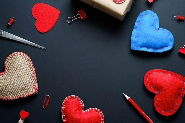 Der hintergrund des valentinstags. rote und blaue büroklammern, wäscheklammern, geschenke, valentinstag, bänder, bleistifte. das konzept der handarbeit.