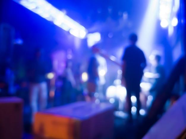Der hintergrund jedoch unscharf des konzerts in einem nachtclub