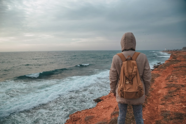 Der hipster-mann, der zum leuchtturm am meer schaut Premium Fotos