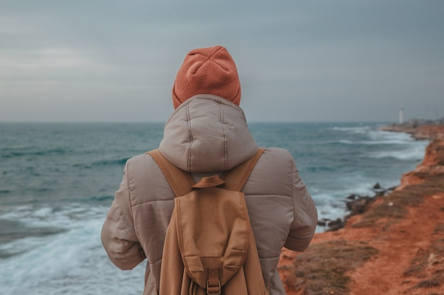 Der hipster-mann, der zum leuchtturm am meer schaut