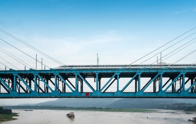 Der hochgeschwindigkeitszug fährt mit hoher geschwindigkeit auf der eisenbahnbrücke.