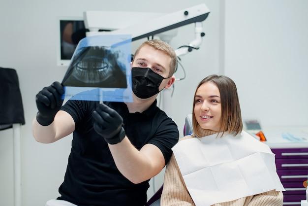 Der hochqualifizierte zahnarzt zeigt der jungen patientin eine röntgenaufnahme der zähne im behandlungsstuhl bei