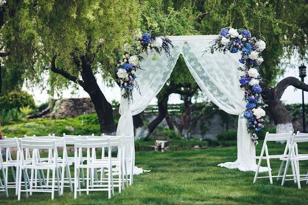 Der hochzeitsbogen ist mit stoff und blumen dekoriert, stühle für gäste. hochzeitszeremonie in der natur.