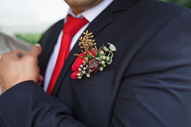 Der hochzeitsboutonniere des bräutigams aus sukkulenten und roten blumen in einer schwarzen jacke mit roter krawatte