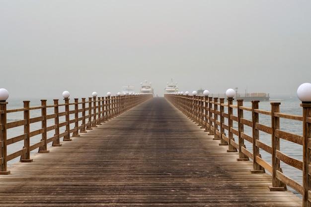 Der hölzerne pier führt zu den schiffen.