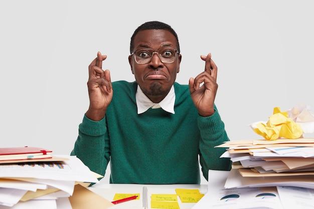 Der hoffnungsvolle elende student sitzt mit gekreuzten fingern am schreibtisch, trägt freizeitkleidung, trägt eine brille und wünscht viel glück bei der aufnahmeprüfung