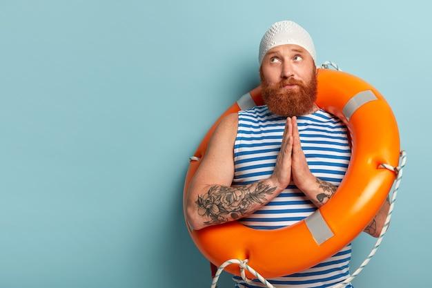 Der hoffnungsvolle, gutaussehende männliche schwimmer hält die handflächen zusammengedrückt, betet für sicheres schwimmen, zieht sich vor ort zurück und trägt eine matrosenweste