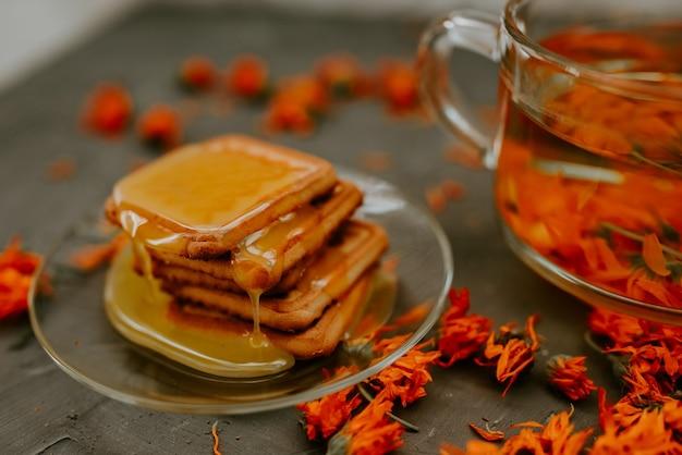 Der honig fließt in einem dünnen strom auf die backwaren. orangen-ringelblumen-blumentee in einer transparenten tasse und mit honig überzogene kekse in einer untertasse
