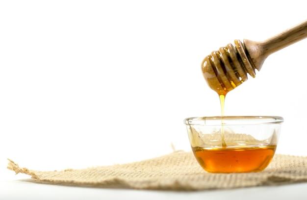 Der honiglöffel und duftender honig in eine transparente schüssel