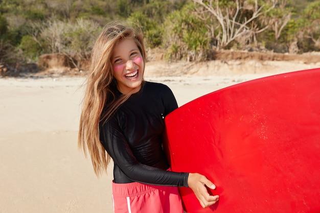 Der horizontale schuss eines fröhlichen professionellen surfers fühlt andrenalin nach wettkämpfen und wellen auf dem meer